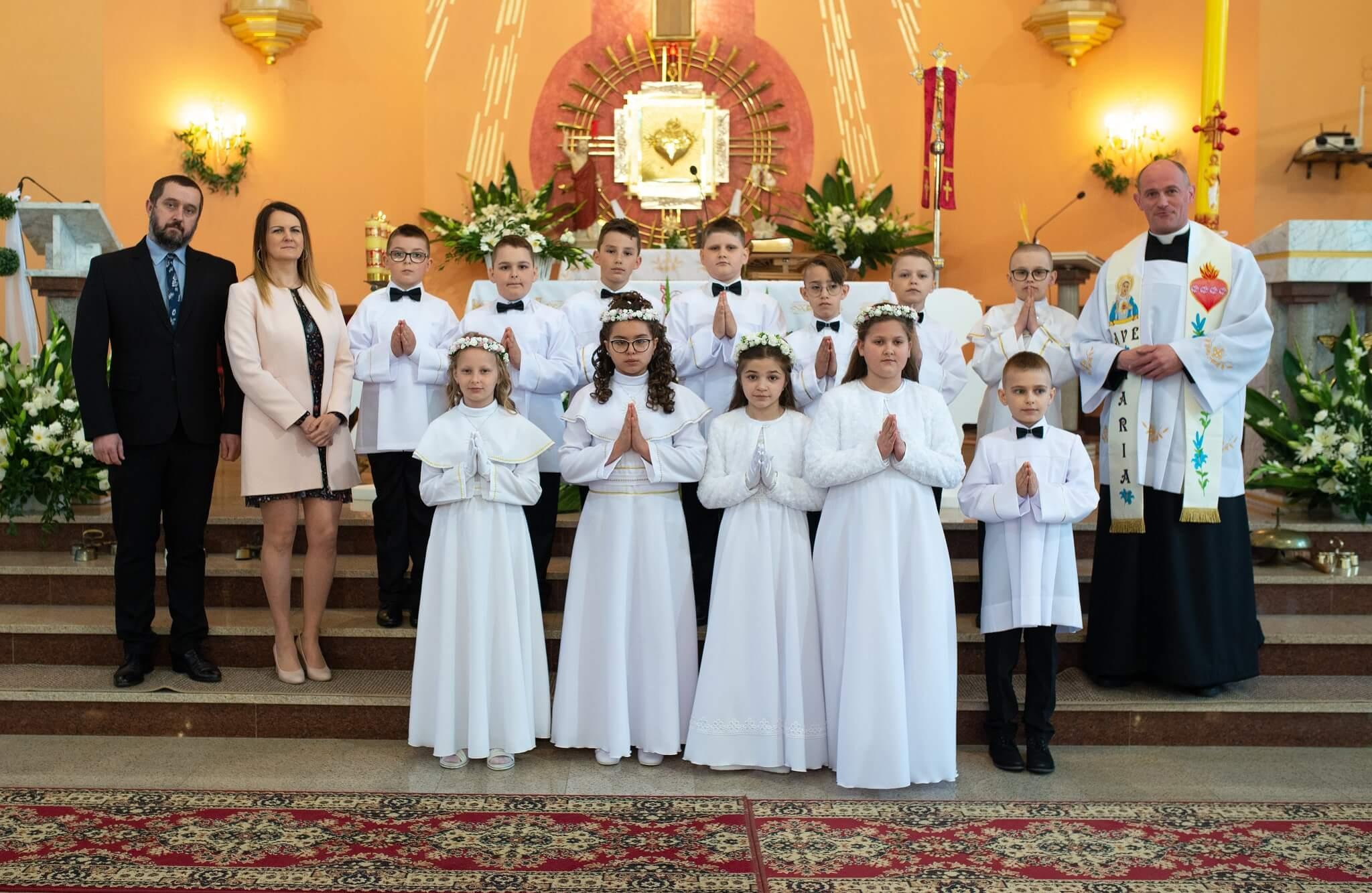 Dzieci komunijne z księdzem proboszczem i nauczycielami